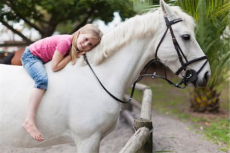 Smiling girl riding horse in yard Stock Photo - Premium Royalty-Free, Code: 649-05649024