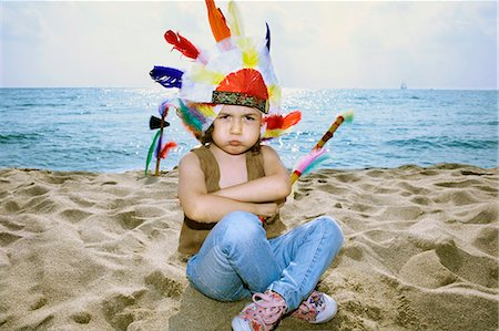 Toddler in Indian headdress on beach Stock Photo - Premium Royalty-Free, Code: 649-05649346