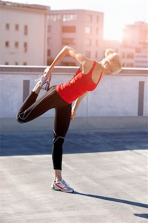 stretching (people exercising) - Runner stretching on rooftop Stock Photo - Premium Royalty-Free, Code: 649-05649581