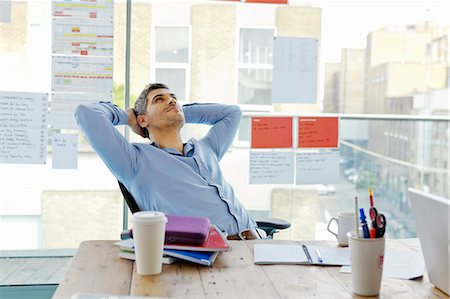 Businessman relaxing at desk in office Stock Photo - Premium Royalty-Free, Code: 649-05656648