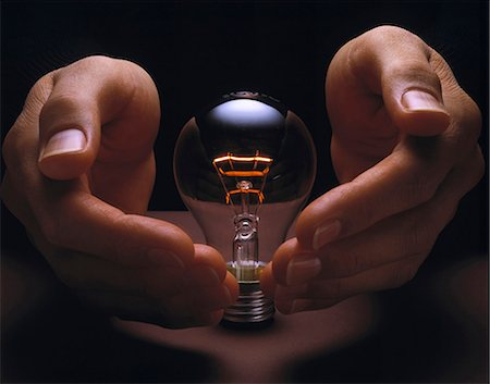 Hands cupping glowing light bulb Stock Photo - Premium Royalty-Free, Code: 649-05656814