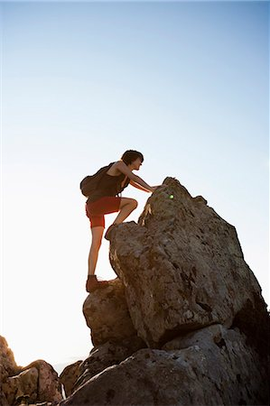Hiker climbing rocks on hill Stock Photo - Premium Royalty-Free, Code: 649-05656876