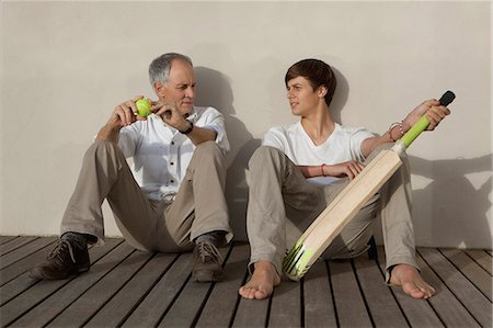 Father and son with cricket bat on patio Stock Photo - Premium Royalty-Free, Code: 649-05656975