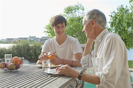 Father and son eating fruit outdoors Stock Photo - Premium Royalty-Free, Code: 649-05656971