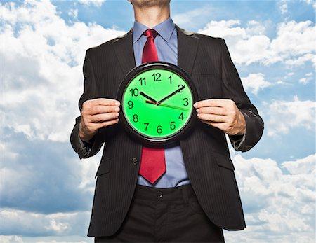 dependable - Businessman holding clock Stock Photo - Premium Royalty-Free, Code: 649-05657041