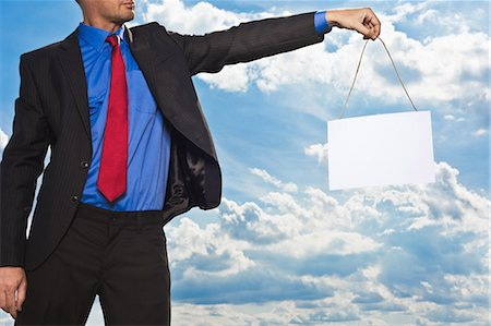 dangling - Businessman holding blank card Stock Photo - Premium Royalty-Free, Code: 649-05657052