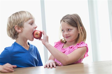 Children eating apple in kitchen Stock Photo - Premium Royalty-Free, Code: 649-05657182