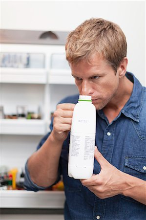 smelly - Man smelling milk jug for freshness Stock Photo - Premium Royalty-Free, Code: 649-05657224