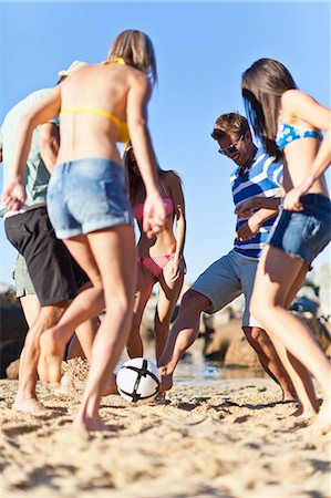 Friends playing soccer on beach Stock Photo - Premium Royalty-Free, Code: 649-05657405