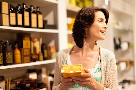 smelling - Woman examining box in store Stock Photo - Premium Royalty-Free, Code: 649-05657443