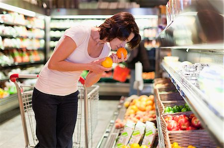 smelling - Woman smelling fruit at grocery store Stock Photo - Premium Royalty-Free, Code: 649-05657455