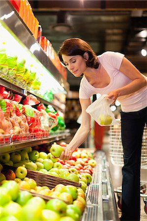 Woman selecting fruit at grocery store Stock Photo - Premium Royalty-Free, Code: 649-05657457