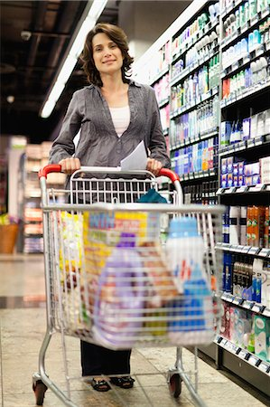 Smiling woman grocery shopping Stock Photo - Premium Royalty-Free, Code: 649-05657476