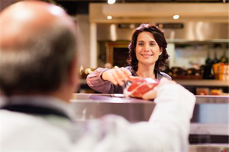 Woman buying meat from butcher Stock Photo - Premium Royalty-Free, Code: 649-05657473