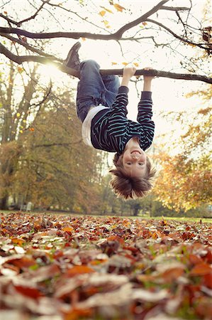 Boy playing on tree outdoors Stock Photo - Premium Royalty-Free, Code: 649-05657651