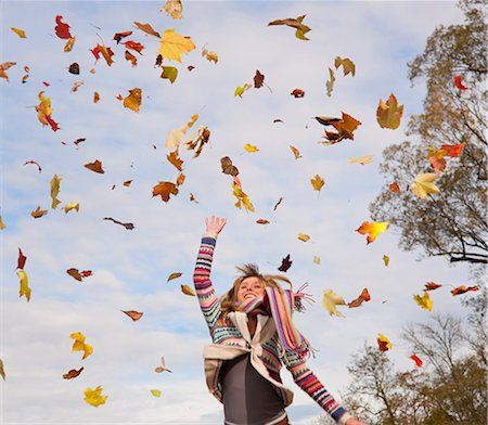 Woman playing in fall leaves Stock Photo - Premium Royalty-Free, Code: 649-05657699