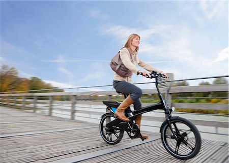 Woman riding bike on wooden walkway Stock Photo - Premium Royalty-Free, Code: 649-05657708