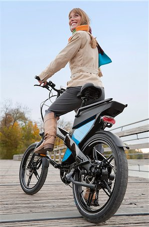 Woman riding bike on wooden walkway Stock Photo - Premium Royalty-Free, Code: 649-05657709