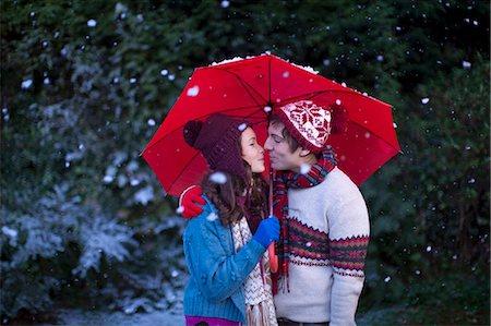 Smiling couple under umbrella in snow Stock Photo - Premium Royalty-Free, Code: 649-05657766