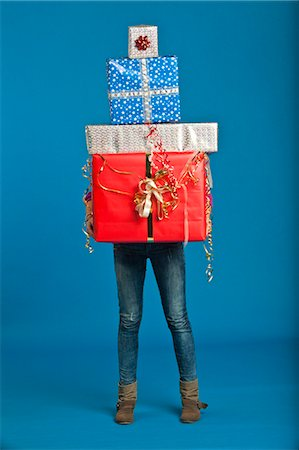 Woman carrying wrapped gifts Stock Photo - Premium Royalty-Free, Code: 649-05657779