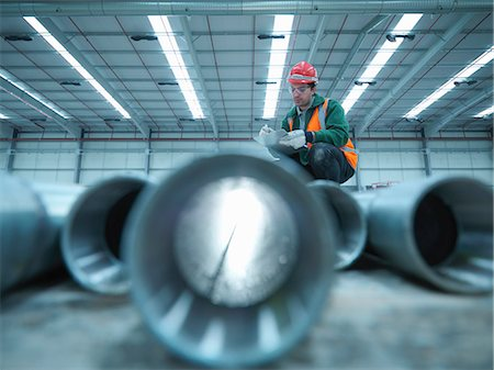 pipe (industry) - Worker examining pipes in warehouse Stock Photo - Premium Royalty-Free, Code: 649-05657969