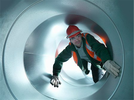 Worker climbing in steel piping Stock Photo - Premium Royalty-Free, Code: 649-05657975