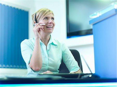 short hair - Businesswoman wearing headset at desk Stock Photo - Premium Royalty-Free, Code: 649-05658068