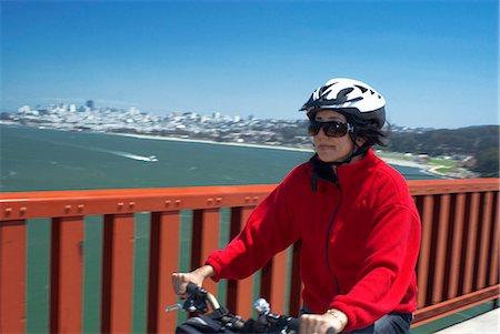 fitness   mature woman - Woman riding bike on urban bridge Stock Photo - Premium Royalty-Free, Code: 649-05658132
