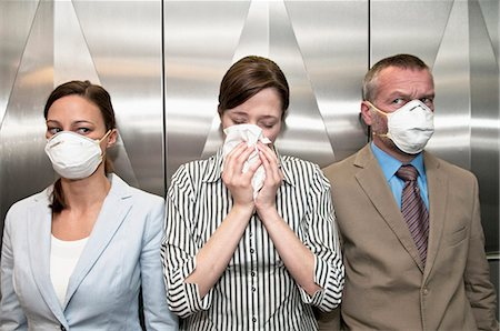 prevention - Woman coughing around others in elevator Stock Photo - Premium Royalty-Free, Code: 649-05658250