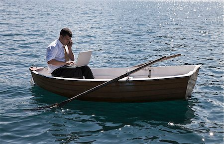 side view of person rowing in boat - Businessman working in rowboat Stock Photo - Premium Royalty-Free, Code: 649-05658402