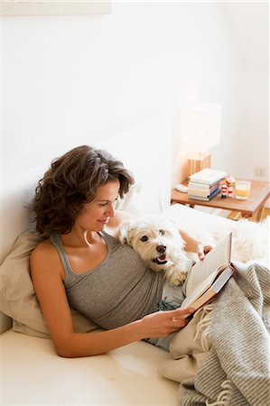 Woman reading with dog in bed Stock Photo - Premium Royalty-Free, Code: 649-05800976