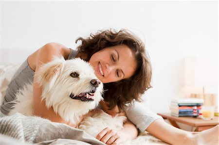 dog and woman and love - Smiling woman petting dog in bed Stock Photo - Premium Royalty-Free, Code: 649-05800977