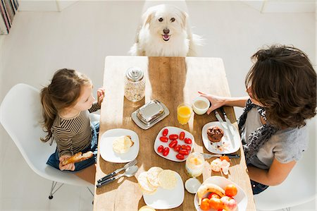 family table eating together - Mother and daughter at table with dog Stock Photo - Premium Royalty-Free, Code: 649-05800981