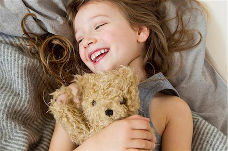 Smiling girl holding teddy bear in bed Stock Photo - Premium Royalty-Free, Code: 649-05801020