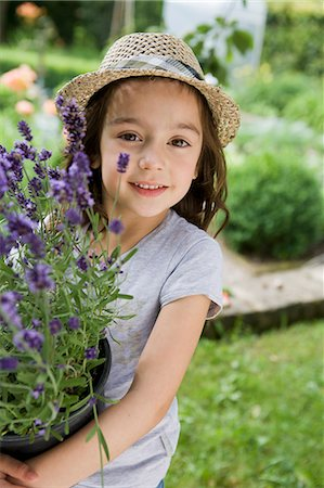 potted plant - Girl carrying potted plants in backyard Stock Photo - Premium Royalty-Free, Code: 649-05801127