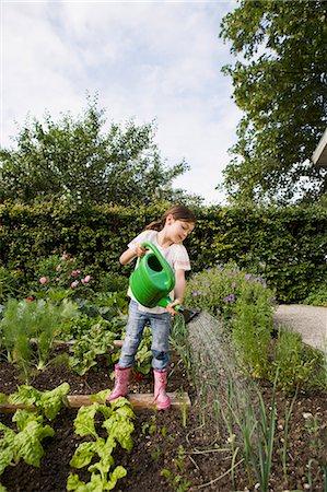 Girl watering plants in backyard Stock Photo - Premium Royalty-Free, Code: 649-05801130