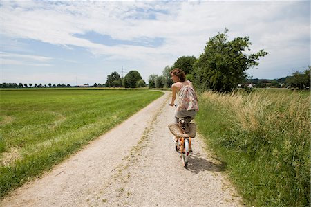 european - Woman riding bicycle on rural road Stock Photo - Premium Royalty-Free, Code: 649-05801147