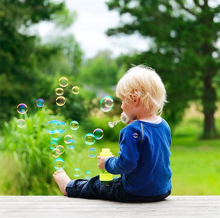 Boy blowing bubbles on porch Stock Photo - Premium Royalty-Free, Code: 649-05801821