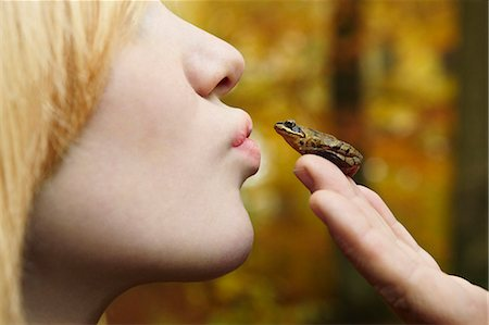 Girl kissing tiny frog in forest Stock Photo - Premium Royalty-Free, Code: 649-05802107