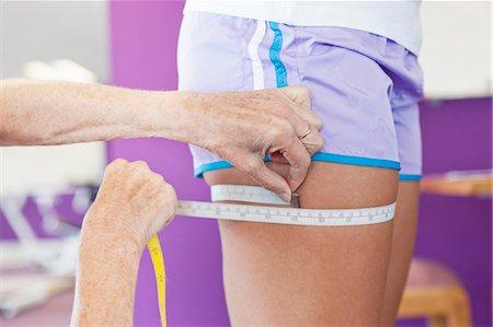 Trainer measuring girls leg in gym Stock Photo - Premium Royalty-Free, Code: 649-05802166