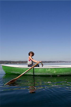 side view of person rowing in boat - Woman rowing boat in still lake Stock Photo - Premium Royalty-Free, Code: 649-05819834