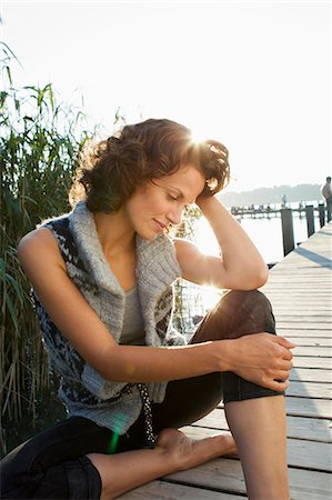 Smiling woman sitting on pier Stock Photo - Premium Royalty-Free, Code: 649-05819878