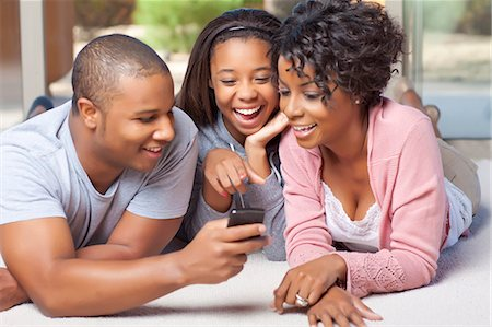 Smiling family using cell phone together Stock Photo - Premium Royalty-Free, Code: 649-05819974