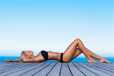 sexi women full body - Woman sunbathing on wooden pier Stock Photo - Premium Royalty-Free, Code: 649-05820079