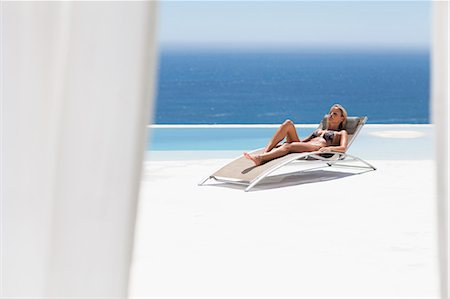 Woman relaxing in lawn chair by pool Stock Photo - Premium Royalty-Free, Code: 649-05820139