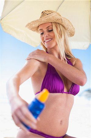 Woman applying sunscreen on beach Stock Photo - Premium Royalty-Free, Code: 649-05820229