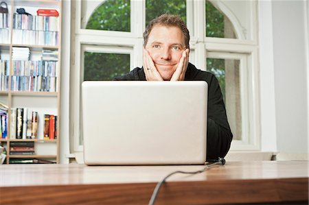 Man at computer with chin in hands Stock Photo - Premium Royalty-Free, Code: 649-05820275