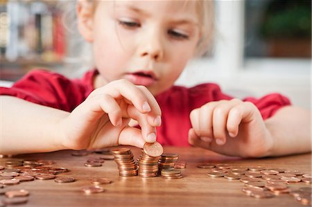 savings - Girl playing with pennies at table Stock Photo - Premium Royalty-Free, Code: 649-05820281