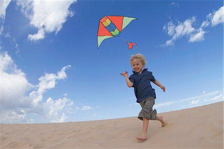 Boy flying kite on sand dune Stock Photo - Premium Royalty-Free, Code: 649-05820295