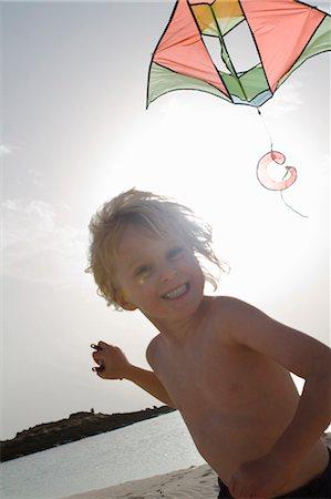 Smiling boy flying kite on beach Stock Photo - Premium Royalty-Free, Code: 649-05820296